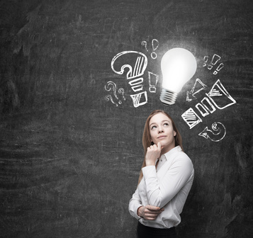 Beautiful business woman is thinking about optimisation measures for business. turned lightbulb and question and exclamation marks