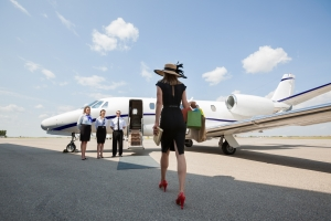Woman Walking Towards Private Jet At Airport Terminal
